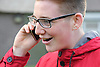 Teenage boy with glasses smiling and talking on mobile phone