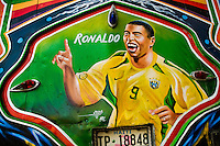 The Brazilian football player Ronaldo painted on the body of a tap-tap bus operating in Port-au-Prince, Haiti, 25 July 2008. Tap-tap vehicles serve as public transportation in Haiti. They are private, operate over fixed routes, departing only when full. Tap-taps are decorated with bright and shiny colors and with a lot of fancy designed elements. There are scenes from the Bible, Christian slogans, TV stars or famous football players often painted on a tap-tap body. Tap-tap name comes from sound of taps on the metal bus body signifying a passenger's request to be dropped off.