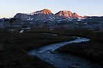 Sunrise on Merriam and Royce Peaks with mountain stream just below Steelhead Lake in the High Sierra mountains over Pine Creek Pass west of Bishop, California, July 2016.