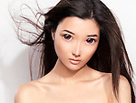 Beauty portrait of a cute young asian woman face with big eyes and flying hair retouched in Japanese anime style