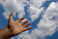 Mans hand reaching for clouds, close-up (Licence this image exclusively with Getty: http://www.gettyimages.com/detail/200471711-001 )