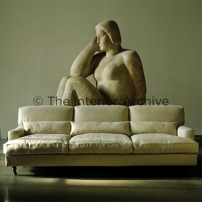 A large stone sculpture of a pensive woman stands behind this deep set sofa upholstered in natural linen