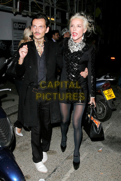 MATTHEW WILLIAMSON & DAPHNE GUINNESS .Leaving the White Cube gallery after party, Dean Street, London, England, .October 14th 2008.full length black coat jacket dress shiny silver bag purse mouth open.CAP/AH.©Adam Houghton/Capital Pictures.