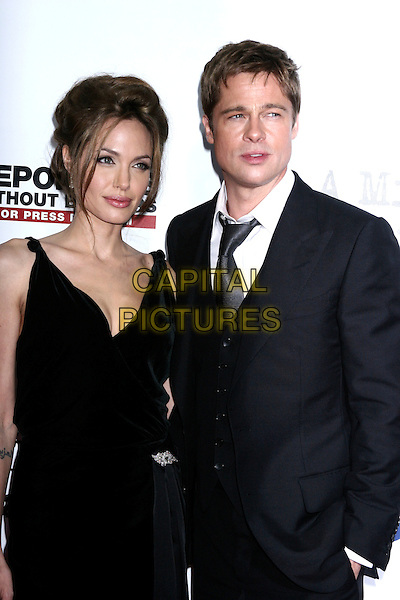 "ANGELINA JOLIE & BRAD PITT.At the premiere of "" A Mighty Heart"" at the Ziefield Theatre, New York, NY, USA..June 13th, 2007.half length black dress suit couple brooch sash hand in pocket.CAP/IW.©Ian Wilson/Capital Pictures"