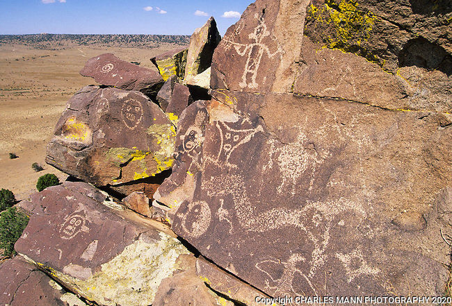 Petroglyphs of a serpent and some man-like figures with haunting faces adorn a volcanic stone surface on a ridge overlooking the Galesteo River Basin near the village of Galesteo, New MeExico