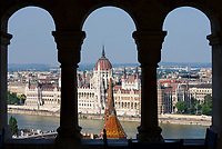 HUN, Ungarn, Budapest, Stadteil Buda, Burgviertel: Blick von Fischerbastei, beliebte Aussichtsterrasse und Wahrzeichen der Stadt, ueber Donauufer zum Parlament, UNESCO Weltkulturerbe, Tuerme einer ehemaligen Kapuzinerklosterkirche am Corvin ter im Vordergrund | HUN, Hungary, Budapest, Castle District: view from Fisherman's Bastion, popular viewpoint and landmark, across Danube embankment towards Parliament, UNESCO World Heritage, spires of former Capuchin monastery church at Corvin Square