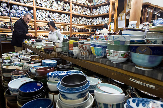 Foreign shoppers look at cups, plates and other items of tableware at Komatsuya, a pottery store in Kappabashi district in Tokyo, Japan on Nov. 10 2010. Often called Tokyo's Kitchen Town, stores in Kappabashi still mainly caters to professionals in the catering industry, though is becoming increasingly popular with foreigners hunting for unique souvenirs. .Photographer: Robert Gilhooly
