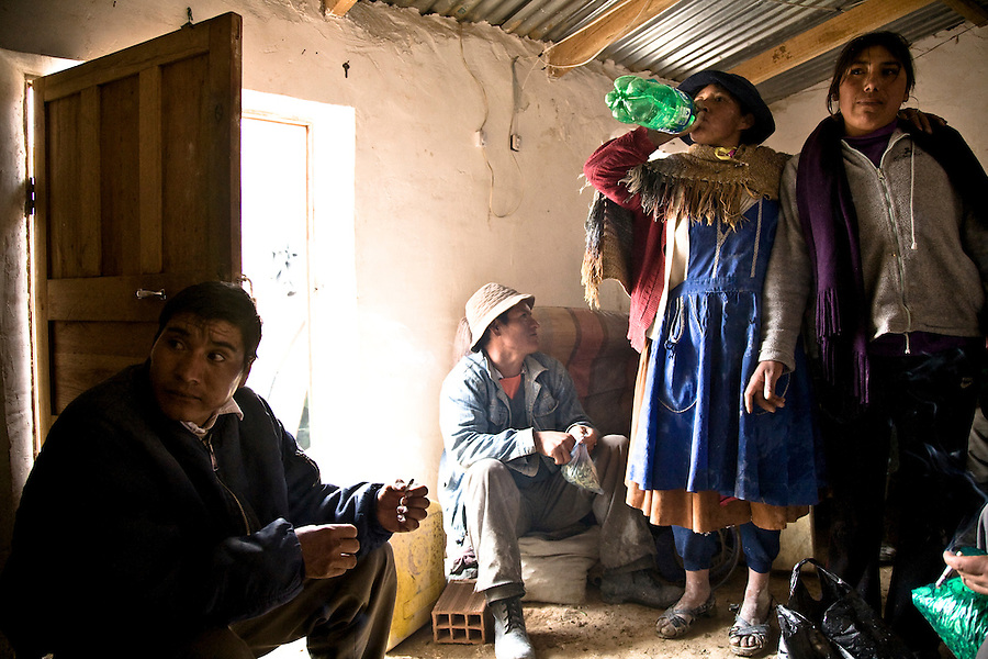 Miners and palliris (women who sort piles of ore outside the mines) resting and chewing coca leaves in a shack owned by the mining cooperative.