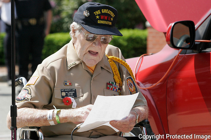 Veteran Capt. Charles Large reads the names of servicemen from Stoughton who was killed during in one of the past wars during one of the Stoughton Memorial Day ceremonies at Stoughton Town Hall on Monday.(Photo by Gary Wilcox).