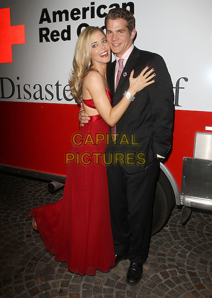 Christina Moore and Guest.Santa Monica Red Cross Chapter Annual Red Tie Gala Held at Fairmont Miramar Hotel, Santa Moinica, California, USA..April 21st, 2012.full length red dress black suit side hug embrace side.CAP/ADM/KB.©Kevan Brooks/AdMedia/Capital Pictures.