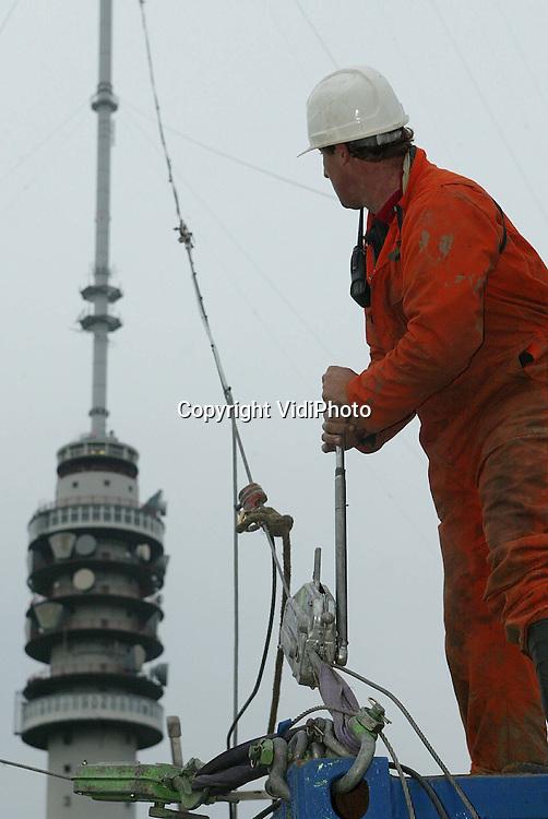 Foto: VidiPhoto..LOPIK - Personeel van Nozema werkt in Lopik aan de grootste kerstboom ter wereld om die op tijd gereed te krijgen. De 375 meter hoge radio- en televisietoren wordt op dit moment opgetuigd met 120 lampen van elk 35 Watt. Op 12 december moet de mast, die verlicht vanaf Hilversum te zien is, gaan branden. Dat de toren dit jaar -en niet eenmaal in de vijf jaar zoals afgesproken- wordt verlicht is bijzonder omdat er eigenlijk geen geld voor was. Sponsors hebben zich garant gesteld voor de kosten.