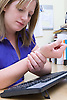 Office worker feeling pain in her wrist; repetitive strain injury (RSI) most commonly affects the neck; shoulders; arms and hands of keyboard workers and other people who continually carry out same tasks and movements in their work,