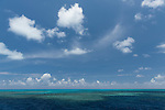 Great Barrier Reef, Australia; blue sky and cloud formations over a shallow section of the Great Barrier Reef