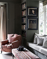 A pale grey window seat in the bay window of the living room offers a tranquil spot for reading
