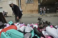 CALI - COLOMBIA, 01-06-2020: Un perro posa sobre zapatos en un comercio callejero en Cali durante el día 69 de la cuarentena total obligatoria en el territorio colombiano causada por la pandemia  del Coronavirus, COVID-19. / A dog poses over a shoes street trade in the city of Cali during the day 69 of mandatory total quarantine in Colombian territory caused by the Coronavirus pandemic, COVID-19. Photo: VizzorImage / Gabriel Aponte / Staff