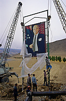 Ashgabat, Turkmenistan, October 1997..Workers raise a giant portrait of President Saparmurat Niyazov in the desert near the Iranian border. Poverty-stricken, but rich in oil and gas resources, this Central Asian former Soviet republic is ruled by the autocratic President Saparmurat Niyazov, or Turkmenbashi as he has renamed himself...............