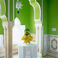A white polyhedron hangs from the ceiling and its green twin sits on a latticework table in a corner of the lime-green study
