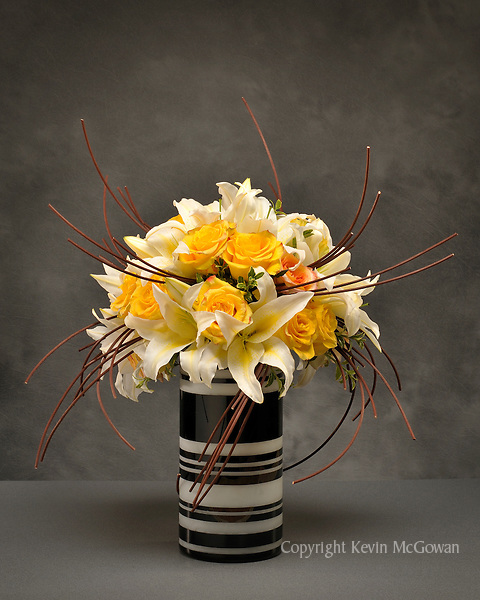 Contemporary flower arrangement of yellow roses and lillies in striped glass vase; floral artist Tomasi Boselawa