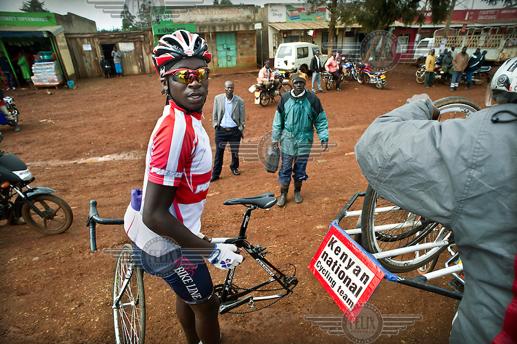 The Kenyan National Cycling Team train along a road between Eldoret and Iten. They stop to change tyres after receiving a puncture along the road. The team is managed by Singaporian Nicholas Leong and trained by Australian Simon Blake.