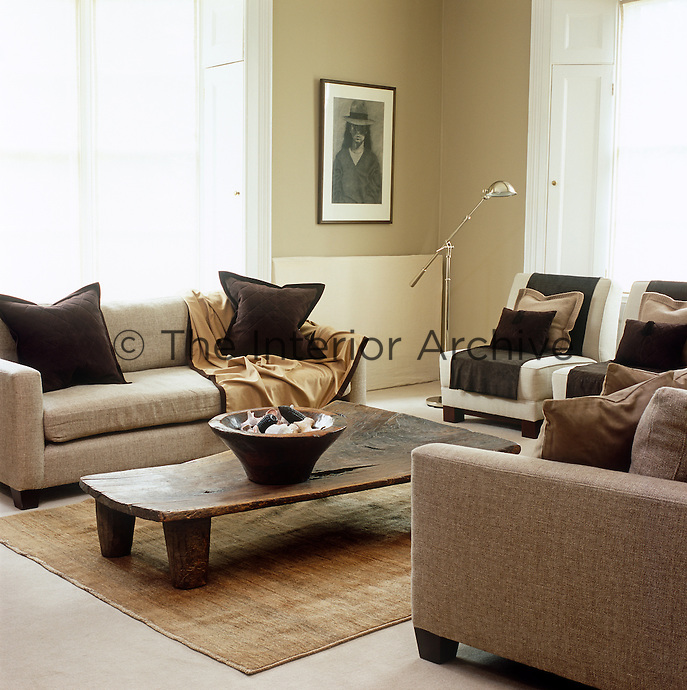The living room of a house in Windsor is a subtle mix of textures and shades of oatmeal and brown and the rugged coffee table was once a West African bed