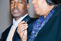 Republican presidential candidate Dr. Ben Carson stands nearby while his wife Candy Carson speaks about reading education at a town hall campaign stop at a meeting of the Windham Republican Town Committee at the Castleton Banquet and Conference Center in Windham, New Hampshire.