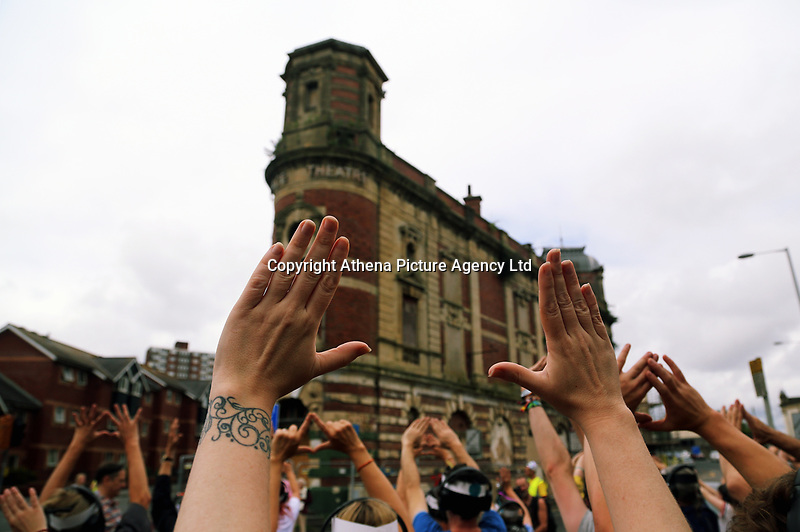 Pictured: A group of levitators concentrate opposite the Palace Theatre in Swansea. Sunday 16 July 2017<br /> Re: A team of highly trained Levitators harness their psychic forces to raise The Palace Theatre on the High Street in Swansea, south Wales, as part of the Troublemakers Festival.<br /> The theatre was built in 1888 as a traditional music hall, named originally the 'Pavilion'. During its lifetime, the building has been used as a bingo hall as well as a gay nightclub.<br /> The Grade II Listed building is one of just two purpose-built music halls left standing in the whole of the UK.<br /> In the early years of the 20th century stars like Charlie Chaplin, Lilly Langtry, Marie Lloyd and Dan Leno filled the venue.<br /> Sir Anthony Hopkins made his first professional stage appearance there in 1960 with Swansea Little Theatre's production of 'Have A Cigarette'.<br /> Also in the early 1960s, Morecambe and Wise were booked. Ken Dodd was the last stand-up comedian to appear there before it became nightclub in the 1970s.<br /> It was also the first place in Wales to show a silent picture and remained undamaged by the blitz that destroyed much of Swansea city centre during the Second World War.<br /> Eventually the theatre was sold for £300,000 to a property company, but in 2010 it was still derelict and actor Edward Fox joined a campaign to have it restored.