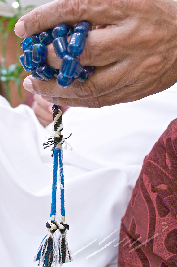 Arab male running the traditional beads, known as misbah or misbaha, between his fingers.