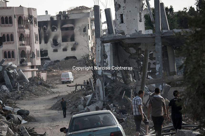 """In this Friday, Aug. 15, 2014 photo, Palestinian civilians go by house buildings destroyed by israeli airstrikes and artillery shelling during the """"Protective Edge"""" military operation in Shayaja neighborhood in Gaza City. After a five days truce was declared on 13th August between Hamas and Israel, civilian population went back to what remains from their houses and goods in Gaza Strip. (Photo/Narciso Contreras)"""