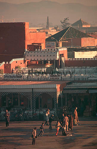 Merchants and kids playing in morning, Djemma al fina market, Marrakesh, Morocco. Atlas mountains in background.