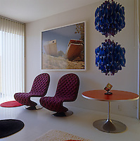 The two purple chairs, side table and pendant light in the bedroom are designed by Verner Panton