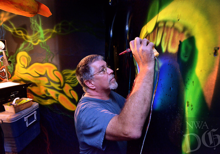 STAFF PHOTO BEN GOFF  @NWABenGoff -- 09/28/14 Danny Smith works on a 3-D blacklight mural inside Nightmare's Haunted House in Bentonville as volunteers prepare the attraction for the season on Sunday September 28, 2014. Smith is creating a maze of murals with layers of special paint that can be viewed in relief with 3-D glasses. The haunted house will open for the Halloween season next Saturday and will feature several new attractions including rides on the new Phantom 13 bus. The haunted house donates much of their profits to their charity sponsor, the Bentonville Breakfast Lions Club.