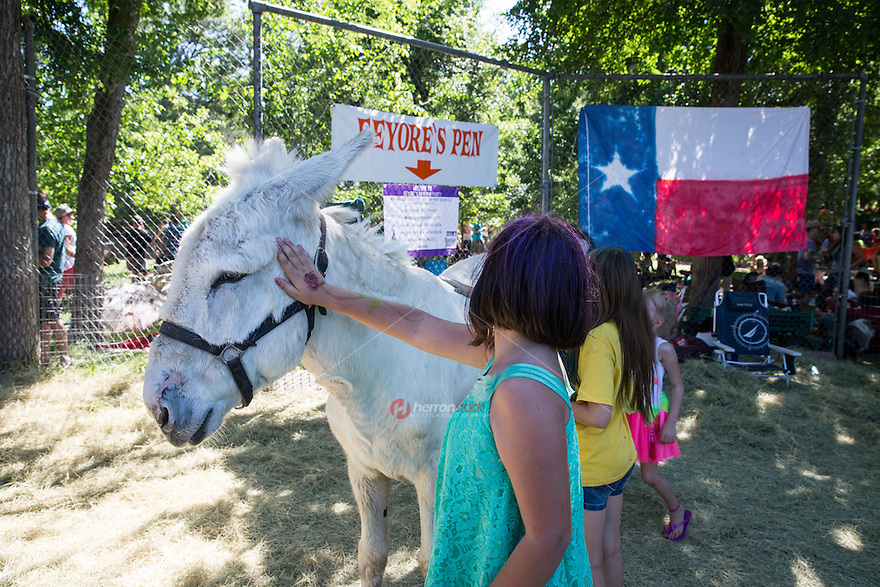 Children pet a donkey to represent Eeyore at the annual Eeyore's Birthday Party in Austin, Texas. Eeyore's Birthday Party is a day-long festival taking place annually since 1963. It typically occurs on the last Saturday of April in Austin's Pease District Park. It includes live music, food and drink vending which benefit local non-profit organizations, attendees in colorful costumes, and very large drum circles. The event is frequented by children and families, with specific events presented for them by the event organizers. The festival is named in honor of Eeyore, a character in A. A. Milne's Winnie-the-Pooh stories.