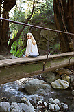 USA, California, Big Sur, Esalen, a woman sits on a small bridge over Hot Springs Creek at the Esalen Institute