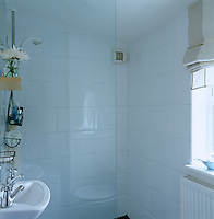 The small bathroom has a walk-in-shower and is decorated with large white wall tiles