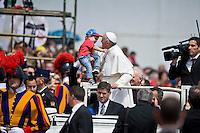 Papa Francesco bacia un bambino durante il saluto ai fedeli in Piazza San Pietro
