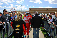 Tony Stewart walks to the media center through a gaggle of fans.