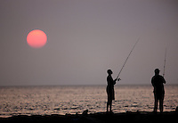 Fishing on the jetty at sunset in village of Menemsha on Martha's Vineyard.  ....