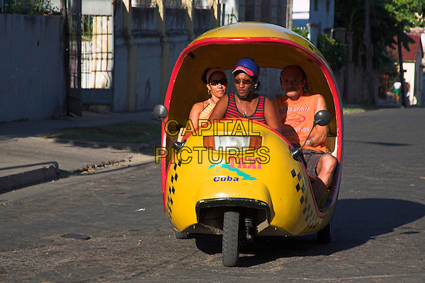 Driver and passengers in yellow three wheeled taxi, Santiago de Cuba, Cuba