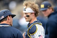 Michigan Wolverines catcher Joe Donovan (0) talks with third base coach Nick Schnabel against the Rutgers Scarlet Knights on April 27, 2019 in the NCAA baseball game at Ray Fisher Stadium in Ann Arbor, Michigan. Michigan defeated Rutgers 10-1. (Andrew Woolley/Four Seam Images)