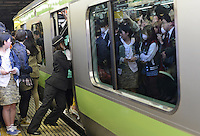 A Railway staff squeezes passengers into full trains during morning rush hour, Shinjuku Station, Tokyo. With up to 4 million passengers passing through it every day, Shinjuku station, Tokyo, Japan, is the busiest train station in the world. The station was used by an average of 3.64 million people per day.  That's 1.3 billion a year.  Or a fifth of humanity. Shinjuku has 36 platforms, and connects 12 different subway and railway lines.  Morning rush hour is pandemonium with all trains 200% full. <br /> <br /> Photo by Richard jones / sinopix