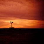 A wind pump set against an orange sky