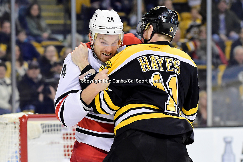 Tuesday, April 5, 2016:  Carolina Hurricanes center Brad Malone (24) and Boston Bruins right wing Jimmy Hayes (11) fight during the National Hockey League game between the Carolina Hurricanes and the Boston Bruins held at TD Garden, in Boston, Massachusetts. Eric Canha/CSM