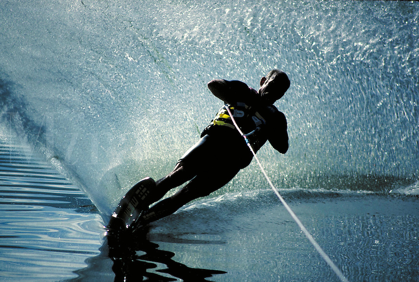 A waterskier lays over in a turn and sprays a wall of water. sports. Dave Weigand. Utah, Pineview Reservoir.