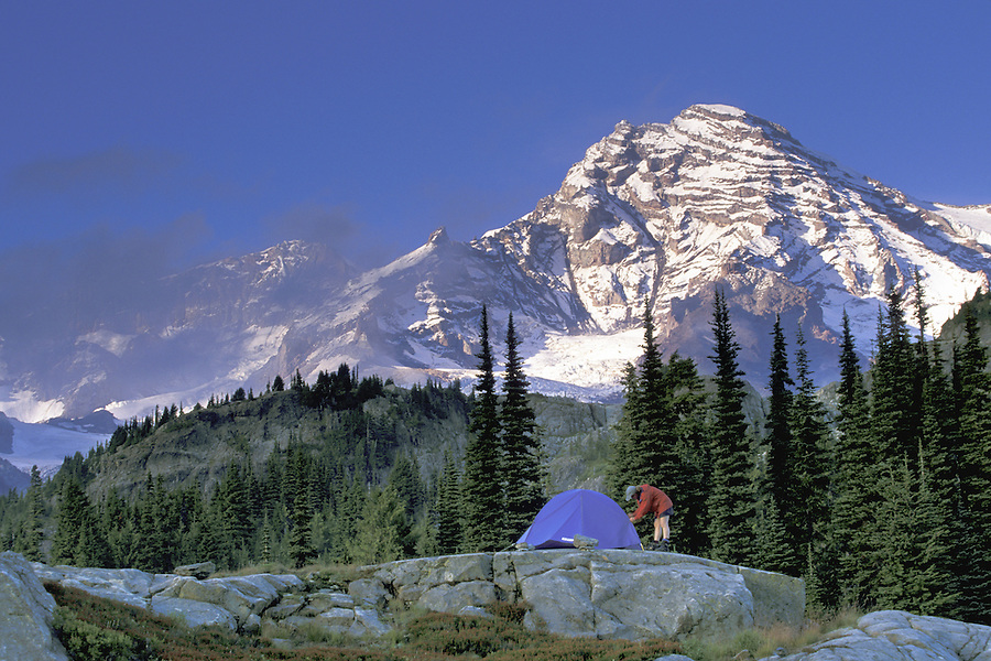 Woman setting up tent below Mount Rainier, Mount Rainier National Park, Washington