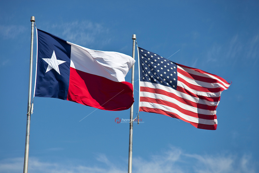 US and Texas flags against blue sky on a bright, sunny, patriotic 4th of July holiday