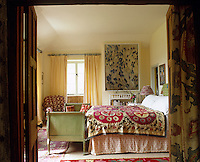 The bedroom is accessorized with a number of ethnic rugs and the bed is covered with a large suzani