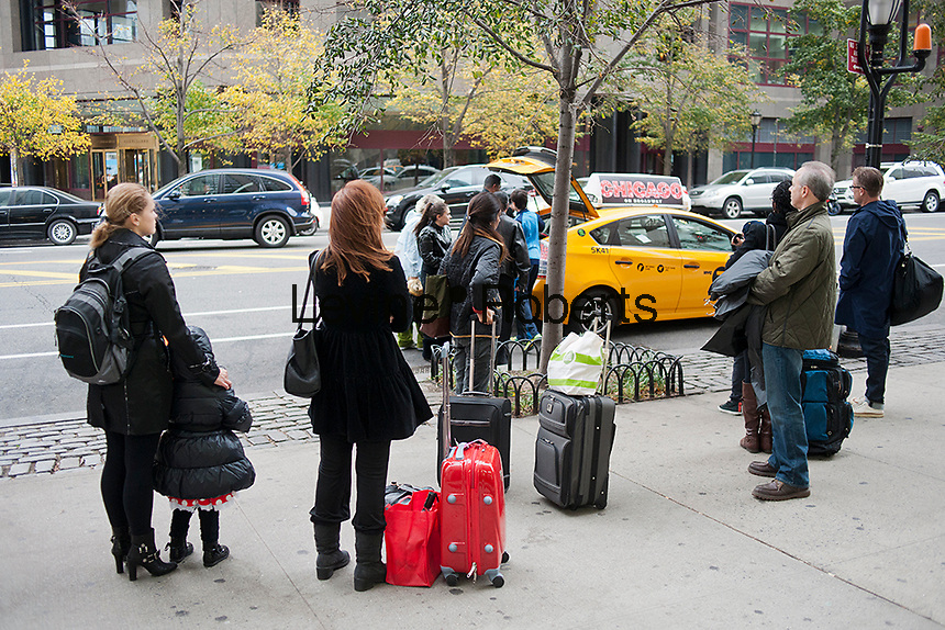 "People with luggage in Battery Park City in the Zone A evacuation zone line up at a taxi stand prior to of Hurricane Sandy, in New York on Sunday, October 28, 2012. In advance of the arrival of Hurricane Sandy New York will shut down the subways at 7 PM on Sunday and evacuate low lying ""Zone A"" areas including Battery Park City. In addition the schools will be closed on Monday. (© Richard B. Levine)"