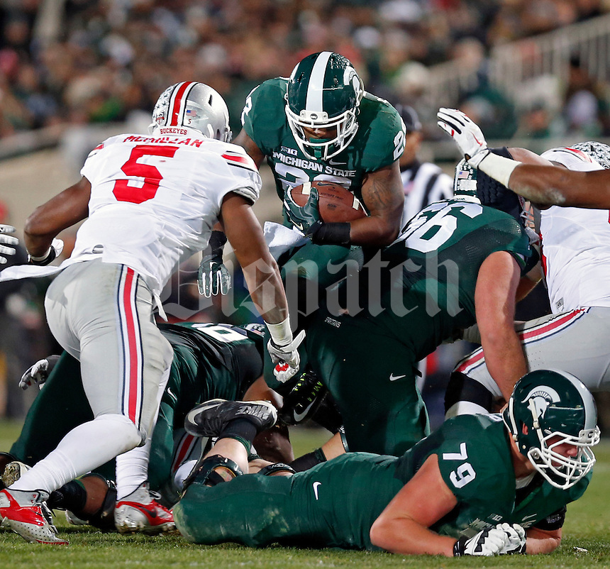 Michigan State Spartans running back Delton Williams (22) hits the hole against the Ohio State Buckeyes defense during the 2nd quarter at Spartan Stadium in East Lansing, Michigan on November 8, 2014.  (Dispatch photo by Kyle Robertson)