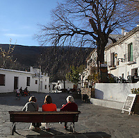 People sitting in the square, Capileira, in the gorge of the Poqueira river, Alpujarra, Andalucia, Southern Spain. Moorish influence is seen in the distinctive cubic architecture of the Sierra Nevada's Alpujarra region, reminiscent of Berber architecture in Morocco's Atlas Mountains. Photograph by Manuel Cohen.