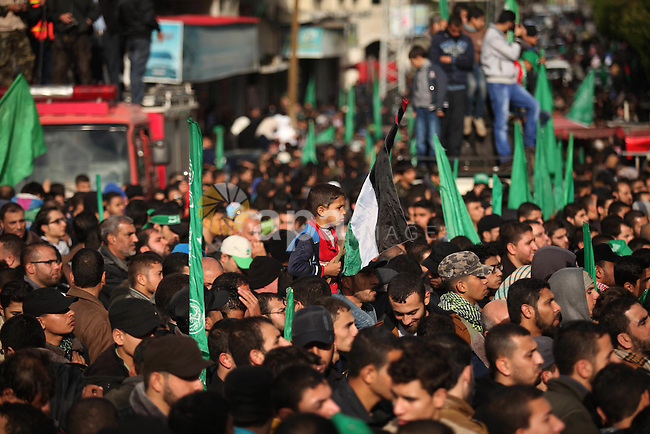 People watch as Palestinian members of al-Qassam Brigades, the armed wing of the Hamas movement, take part in a military parade marking the 27th anniversary of Hamas' founding, in Gaza City December 14, 2014. Photo by Ashraf Amra